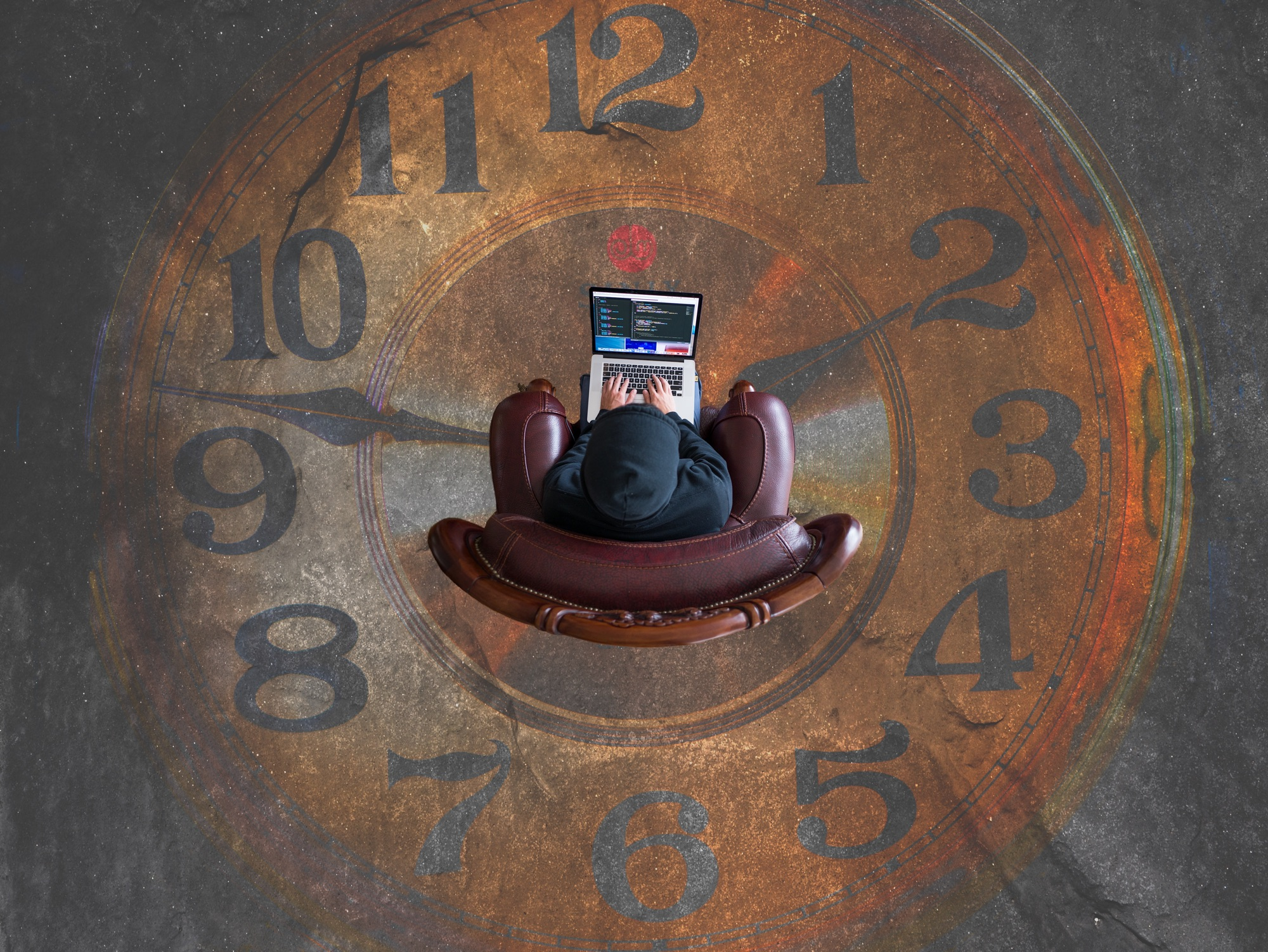 Person sitting on top of a clock dial with a MacBook on their lap